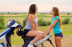 Two beautiful girls resting after riding scooter. On sunny summer day Stock Photo