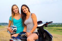 Two beautiful girls resting after riding scooter Royalty Free Stock Photo