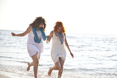 Two beautiful girls running on the beach. Royalty Free Stock Images