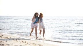 Two beautiful girls running on the beach. Stock Photo