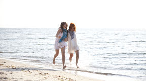 Two Beautiful Girls Running On The Beach. Stock Photo