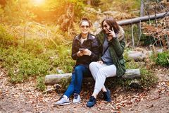 Two beautiful girls sat down in the forest Stock Photo