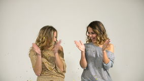 Two beautiful girls in shiny blouses throw confetti on a white background. Slowmotion stock footage