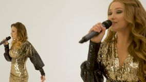 Two beautiful girls in shiny dresses dancing and singing in the studio on a white background. Record a music video stock video footage