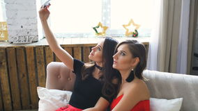 Two beautiful girls shoot selfie while sitting on sofa. Girlfriends having fun laugh in bedroom. stock video footage