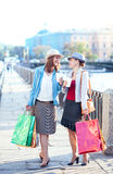 Two beautiful girls with shopping bags and cup of coffee Stock Photo
