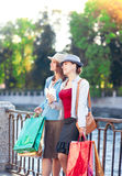 Two beautiful girls with shopping bags and cup of coffee in the Royalty Free Stock Photos