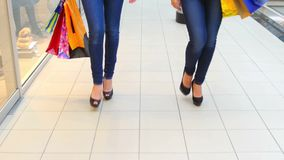 Two beautiful girls with shopping bags goes on. Shopping center stock footage