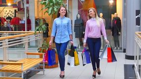 Two beautiful girls with shopping bags goes on. Shopping center. Slow motion stock video footage