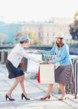 Two beautiful girls with shopping bags having fight in the city. Outdoor Royalty Free Stock Photos