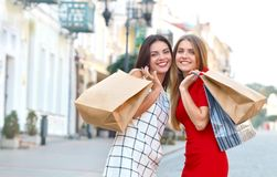 Two beautiful girls with shopping bags look back stock images