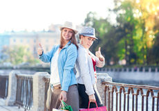 Two beautiful girls with shopping bags showing thumbs up Royalty Free Stock Image