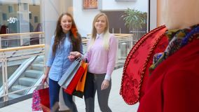 Two beautiful girls with shopping bags suited to. Showcase at the mall stock footage
