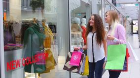 Two beautiful girls with shopping bags suited to. Showcase at the mall stock video