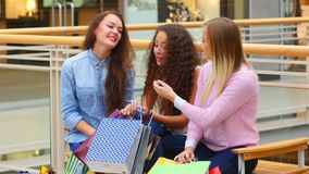 Two beautiful girls with shopping bags watch. Purchase on shopping center stock video footage