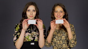 Two beautiful girls show blank business card. stock video footage
