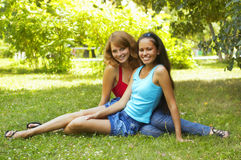 Two beautiful girls sit in park Royalty Free Stock Image