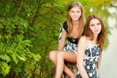 Two beautiful girls sit on stub Royalty Free Stock Image