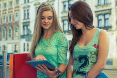Two beautiful girls sitting on a bench with tablet pc. Stock Photos