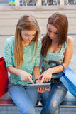 Two beautiful girls sitting on a bench with tablet pc. Royalty Free Stock Photography