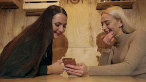 Two beautiful girls sitting in a cafe with phone and smiling. Technology stock video