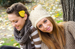 Two beautiful girls sitting in colorful autumn park Royalty Free Stock Photo