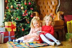 Beautiful girls are sitting on the floor near the festive Christmas tree royalty free stock photography