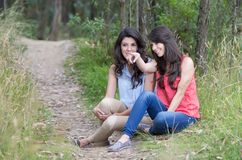 Two beautiful girls sitting in a forest Royalty Free Stock Image