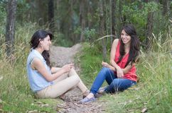 Two beautiful girls sitting in a forest Stock Photography