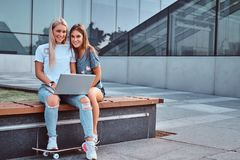 Two beautiful girls sitting holds a laptop and looking at a camera while sitting on the bench on background of the stock photography