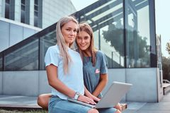 Two beautiful girls sitting holds a laptop and looking at a camera while sitting on the bench on background of the royalty free stock images