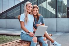 Two beautiful girls sitting holds a laptop and looking at a camera while sitting on the bench on background of the stock images