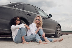 Two beautiful girls sitting at the machine on the beach royalty free stock photo