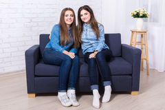 Two beautiful girls sitting on sofa in living room Royalty Free Stock Images