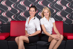 Two beautiful girls sitting on the sofa Royalty Free Stock Photos