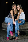 Two beautiful girls sitting on a stone Stock Images