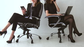 Two Beautiful Girls Sitting and Talking to Their Clients at The Office. They are Selling Some Product on Phone stock footage