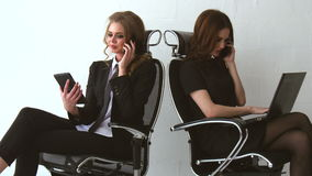 Two beautiful girls sitting and talking to their clients at the office. They are Selling Some Product on Phone stock video footage