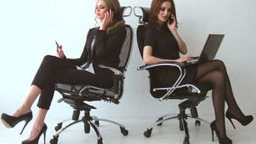 Two beautiful girls sitting and talking to their clients at the office stock video footage