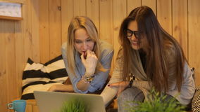 Two beautiful girls smilling and use laptop. Two beautiful girls talking and use laptop in cafe stock video footage