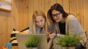 Two beautiful girls smilling and use laptop. Two beautiful girls talking and use laptop in cafe stock footage