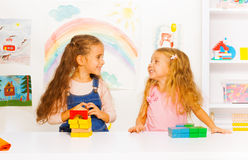 Two beautiful girls stacking blocks Royalty Free Stock Photos
