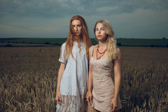 Two beautiful girls standing in a field Stock Photos