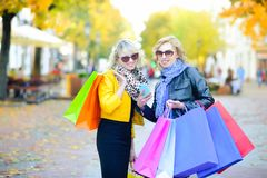 Two beautiful girls standing on the street with shopping packages make an order by phone royalty free stock photography