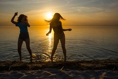 Two beautiful girls, students are dancing on the beach at sunset. Background, silhouettes Stock Photos