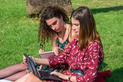 Two beautiful girls are studying for exams on tablet stock image