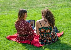 Two beautiful girls are studying for exams on tablet royalty free stock image
