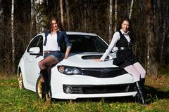 Two beautiful girls and stylish white sports car Stock Photos