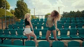 Two beautiful girls at sunny day have fun and dancing at grandstand in slomo. Two young stylish womans dancing at tribune. Beautiful girls at sunny day have fun stock footage