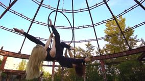 Two beautiful girls are swinging on the ring for aerial acrobatics, slow motion. Blonde and brunette in tight clothes perform synchronous stunts on the ring for stock video footage
